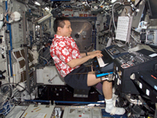 Edward Lu plays a musical keyboard during off-shift time during Expedition 7