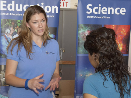 NASA Dryden's student and faculty programs coordinator Kendra Titus discusses career interests with a high school student in front of the SOFIA exhibit at Salute to Youth.