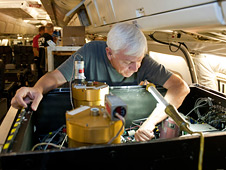 Glen Sachse of NASA's Langley Research Center adjusts an instrument on NASA's DC-8 flying laboratory.