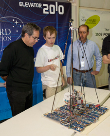 Nick Burrows of the winning LaserMotive team explains details of his team's robotic climber to NASA Dryden center director Dave McBride as NASA Centennial Challenge program director Andy Petro looks on.