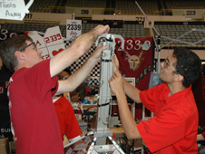 Antelope Valley High School robotics team mentor Myrle McLernon and team member Kenny Hermosillo adjust the grapple on the hoisting arm of their robot during a break in the FIRST Robotics regional competition in Long Beach March 20.