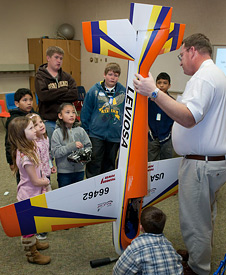 Jerry Budd shows off his competition model aircraft to kids.