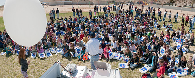 Students at the West Boron Elementary School gather to watch as a student prepared to launch a weather balloon.