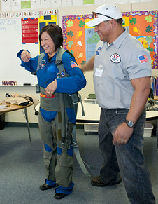 Nancy Pena shows off a high-G flight suit used by NASA pilots.
