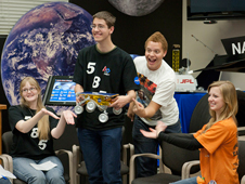 Four American teens clown around with a model of one of NASA's Mars Rovers during the interactive video link with Indonesian teens via NASA's Distance Learning Network.