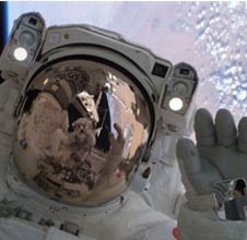 An astronaut floating high above Earth wears a white spacesuit