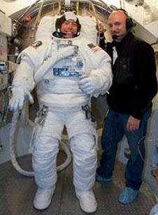 An astronaut dressed in a white spacesuit stands beside a man wearing regular clothes and a headset