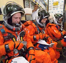 Three astronauts dressed in orange shuttle launch and entry suits sit reading papers