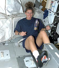 Astronaut Sandra H. Magnus wearing exercise clothes while riding an exercise bike