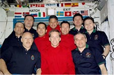 Ten astronauts dressed in red or blue shirts on the space station