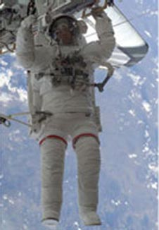 An astronaut takes a spacewalk in a white spacesuit