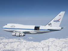 With the sliding door over its 17-ton infrared telescope wide open, the SOFIA soars over California's snow-covered Sierra Nevada range on a test flight.