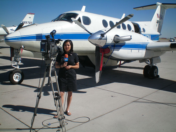 Rina Nakano of KCWY-TV, Ch. 13 in Casper, Wyo., does a stand-up report in front of NASA 801, a Beechcraft B-200 King Air.