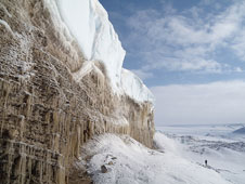 A scenic view of Greenland's icy cliffs is displayed.