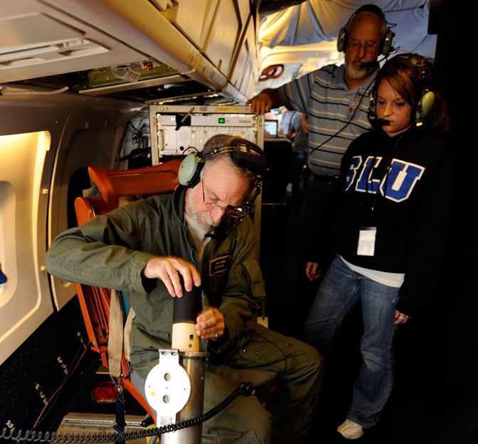 Errol Korn, seated left, deploys a dropsonde experiment over the Gulf of Mexico during a flight aboard NASA's DC-8 flying laboratory as Janel Thomas, a University of Maryland graduate student, and Bob Pasken look on.