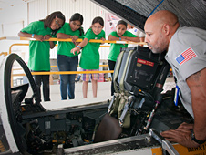 Aircraft mechanic Daren Ware explains cockpit instruments in a NASA F/A-18 mission support aircraft to a group.