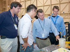 Patrick Chan, second from left, explains components of the Dryden-developed fiber optic strain sensing technology to Bobby Braun, second from right. Also in the photo are Tom Horn, left, and Robbie Schingler, right.