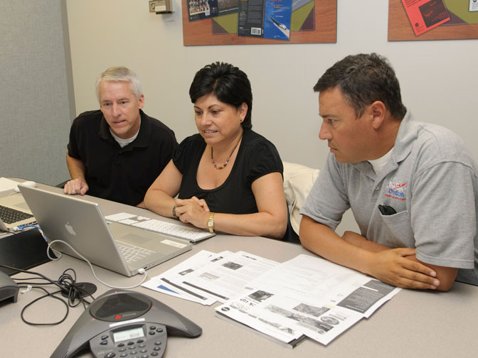 NASA Dryden Global Hawk and Ikhana unmanned aircraft pilot Herman Posada assisted by NASA Dryden public affairs staffer Gray Creech and translator Carmen Arevalo, participate in NASA's first bi-lingual Internet web chat Sept. 21.