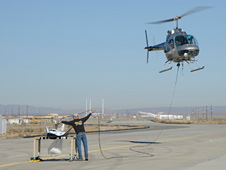 Helicopter prepares to lift Dream Chaser scale model.