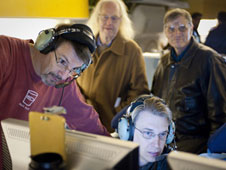 Jim De Buizer, lower right, studies data with FORCAST instrument principal investigator Terry Herter, left. In the background, Eric Becklin and Allan Meyer, right, look on during preparations for the initial SOFIA science flight