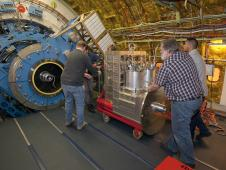 NASA and German scientists and technicians move the GREAT instrument near the Stratospheric Observatory for Infrared Astronomy's telescope prior to mounting.