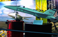 A four-foot scale model of NASA's Active Aeroelastic Wing in front of a photo of the real aircraft