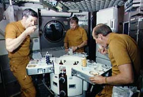 The first Skylab crew enjoys a meal in space.