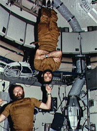 Astronauts Carr and Pogue demonstrate weight training in zero-gravity.
