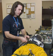 Full pressure suit technician, Joshua Graham performs a pre-flight inspection of a pressure suit in support of NASA's ER-2 high altitude flight operations.