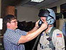 Jeff Greulich, DynCorp life support technician, adjusts a prototype helmet on pilot Craig Bomben.