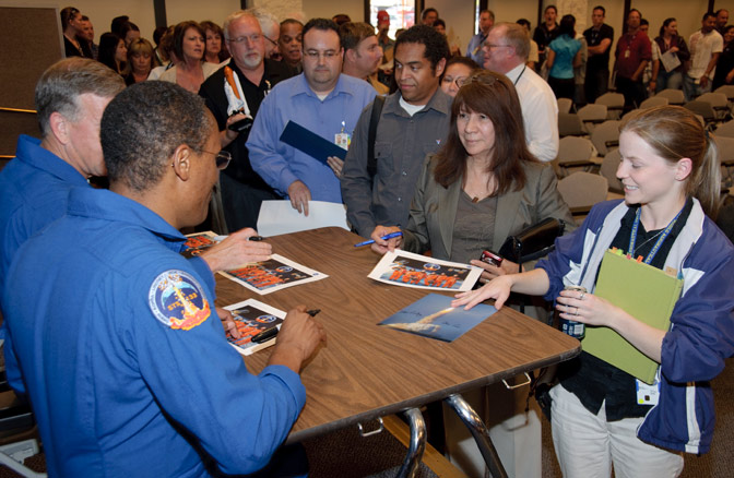 STS-133 astronauts Steve Lindsey and Alvin Drew autograph launch and crew photos.