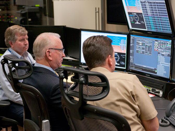Congressman Howard P. McKeon reviews flight deck displays in the Global Hawk Operations Center with project manager Chris Naftel, at left, and deputy project manager Phil Hall, at right.
