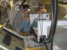 Broadband lidar instrument team members Wen Huang and Elena Georgieva test the performance of their laser in the belly of the DC-8 at the NASA Dryden Aircraft Operations Facility
