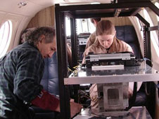 NASA Goddard engineer Murzy Jhabvala and NASA Dryden mission director Brittany Wells check out instrumentation during a Caves Detection Project flight.