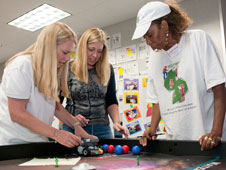 Lancaster teachers Bobbie Mitchell and Michelle Reynolds and Dolores Williams of Millionaire Minds Kids in Apple Valley check out their Lego robot during the robotics workshop.