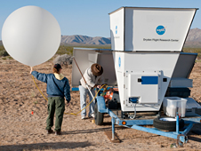 NASA Dryden meteorologists Fran Houtas and Scott Wiley prepare to launch a weather balloon next to a SODAR unit.