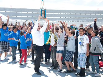 Mojave Elementary School students erupt in cheers as principal Marv Baker lofts their trophy for winning the Mojave Rocket Challenge.