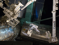 Spacewalker Mike Fossum rides on the International Space Station's robotic arm.