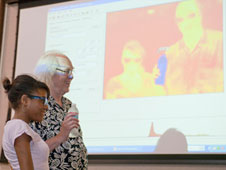 Eric Becklin and a volunteer demonstrate that while heat from faces shows up in the infrared spectrum, cold objects, like a water bottle, appear dark.