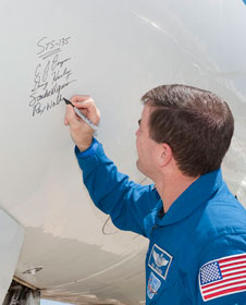 NASA astronaut Rex Walheim adds his autograph to those of his STS-135 crewmates Chris Ferguson, Doug Hurley and Sandra Magnus on the nose of NASA 944, a modified Gulfstream-II Shuttle Training Aircraft following their visit to NASA Dryden Aug. 23.