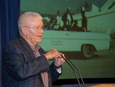 Fred Haise spoke to Dryden employees at the main campus on Aug. 11 about his work at the center, which included flying research aircraft such as the M2-F1, with its Pontiac tow vehicle on the screen behind him.