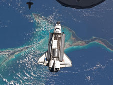 Space shuttle Atlantis is photographed from the International Space Station as it flies over the Bahamas prior to docking with the station. The Raffaello multipurpose logistics module can be seen inside the shuttles cargo bay.