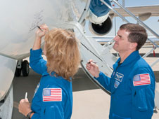 STS-135 mission specialists Sandy Magnus and Rex Walheim autograph a modified G-II Shuttle Training Aircraft Dryden recently acquired.