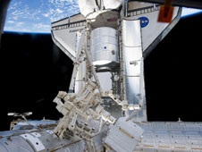 The docked space shuttle Discovery and the Canadian-built Dextre, also known as the Special Purpose Dexterous Manipulator, were photographed by an STS-133 crewmember on the International Space Station. The blackness of space and Earth's horizon provide the backdrop.