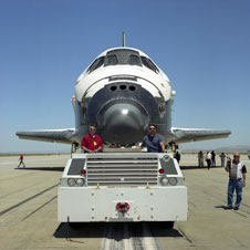 Dryden shuttle worker Phil Burkhardt, right, and an unidentified employee tow Endeavour to Dryden's Mate/Demate Device following the completion of STS-100 at Edwards on May 1, 2001.