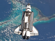 Space shuttle Atlantis is photographed from the International Space Station as it flies over the Bahamas prior to docking with the station. The Raffaello multipurpose logistics module can be seen inside the shuttle's cargo bay.