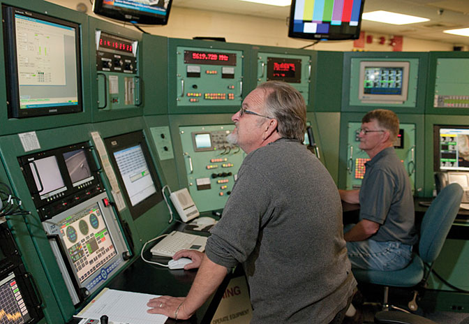 Mike Webb and Rick Dykstra are seen at the radar and triplex consoles, tools used by Western Aeronautical Test Range staff to support space shuttles on orbit and during landings at Dryden and to maintain communication with the International Space Station.