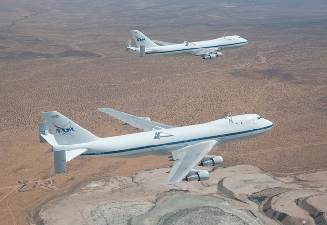 NASA's 747 Shuttle Carrier Aircraft No. 905, foreground, and No. 911, background, fly in formation over the Rio Tinto borax mine west of Boron, Calif.