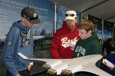 Bryce Matanis, Vern Thomas and T.J. Thomas examine a model of NASA's hybrid wing body aircraft at the NASA exhibit in Albuquerque.
