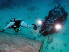Engineering evaluations by topside personnel in preparation for having the crew work with the Deep Worker submersibles as Space Exploration Vehicle analogs; note the custom designed foot restraint and magnetic stinger for docking with the rock wall simulating an asteroid surface. Photo credit: NASA